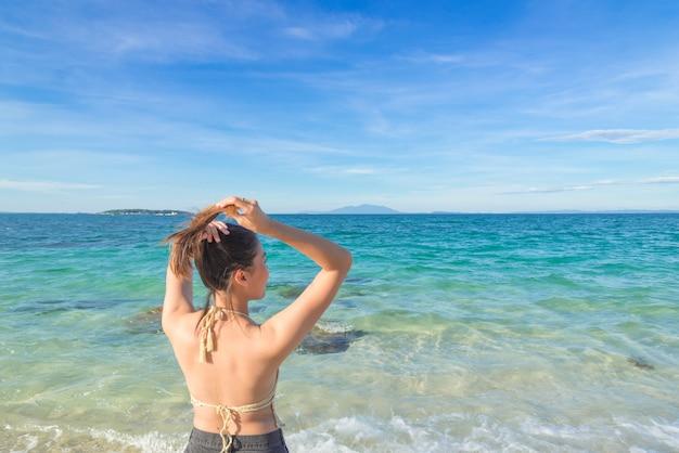 Ritratto di estate all'aperto di giovane donna graziosa che guarda all'oceano in spiaggia tropicale