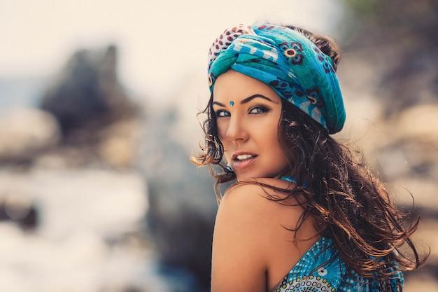 Ritratto di estate all'aperto di giovane donna graziosa in abiti in stile orientale e accessori sulla spiaggia