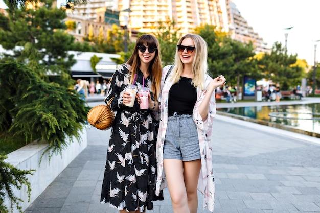 Ritratto di estate di due eleganti e graziose migliori amiche che si divertono insieme, sorridono e godono del tempo in strada, vestiti alla moda eleganti implora e occhiali da sole, coppia felice, relazioni.