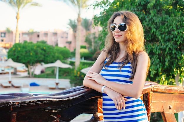 Ritratto di estate di giovane donna attraente con occhiali da sole in località