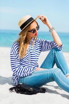 Ritratto di estate di giovane donna fresca in occhiali da sole freschi e cappello di paglia seduto sulla soleggiata spiaggia tropicale