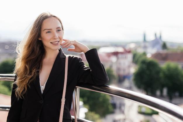 Ritratto di estate di giovane donna rilassante sulla terrazza sul tetto su sfondo vista città europea.