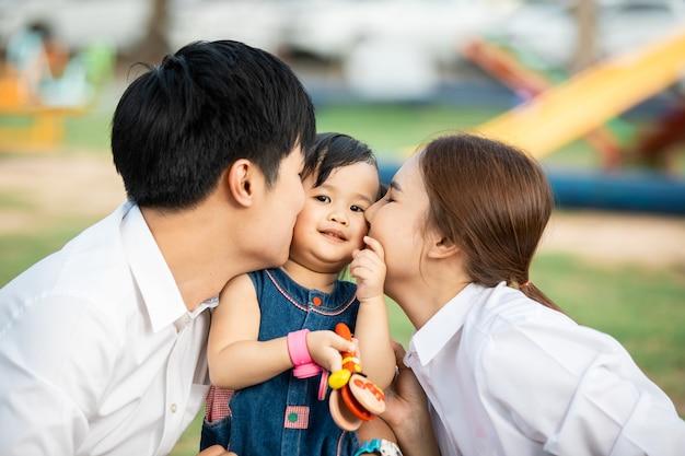 Ritratto di famiglia asiatica con gente felice che sorride al parco.