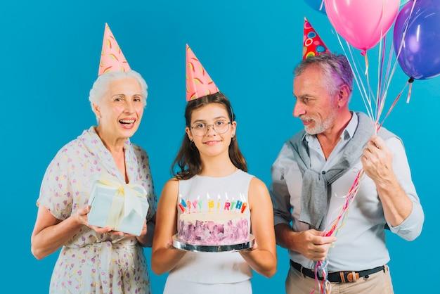 Ritratto di famiglia con torta di compleanno; regalo e palloncini su sfondo blu