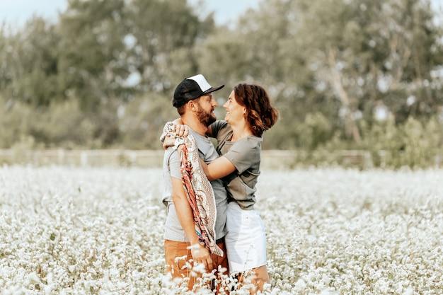 Ritratto di famiglia di una giovane bella coppia su un campo bianco con fiori