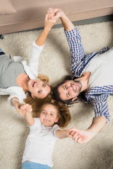 Ritratto di famiglia di vista superiore che mette su tappeto