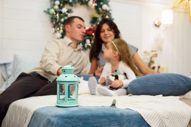 Ritratto di famiglia felice a natale, madre, padre e figlio seduti sul letto a casa, decorazione di chritmas intorno a loro.