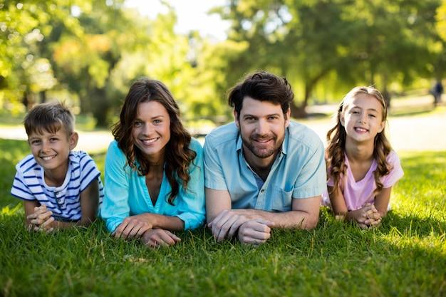 Ritratto di famiglia felice sdraiato sull'erba nel parco