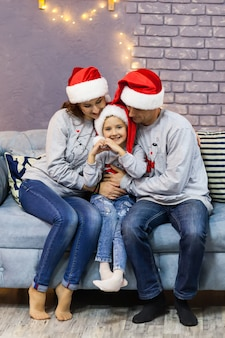 Ritratto di famiglia in tappi rossi di babbo natale