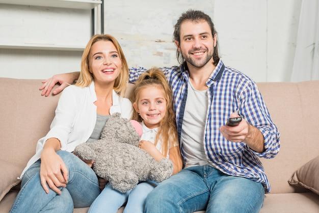 Ritratto di famiglia sul divano con orsacchiotto