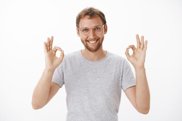 Ritratto di felice, amichevole e sicuro di sé bello uomo barbuto in bicchieri alzando entrambe le mani su ok o eccellente gesto sorridente assicurando che il lavoro sarà fatto in tempo
