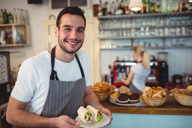 Ritratto di felice barista con panini freschi