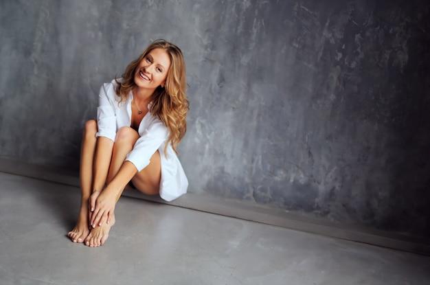 Ritratto di felice bella donna sorridente. affascinante ragazza in abiti bianchi