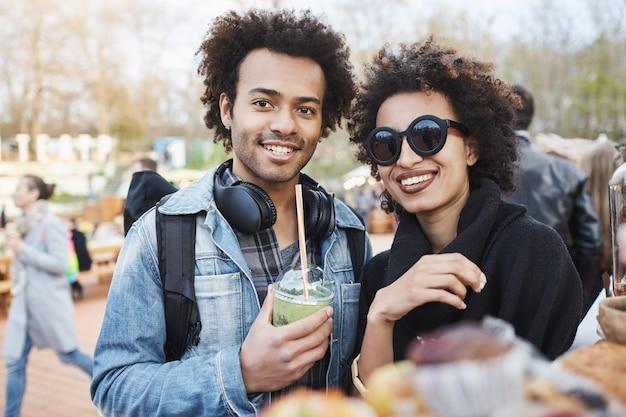 Ritratto di felice coppia carina dalla carnagione scura con acconciatura afro, passeggiando per il festival gastronomico, degustazione e bere cocktail