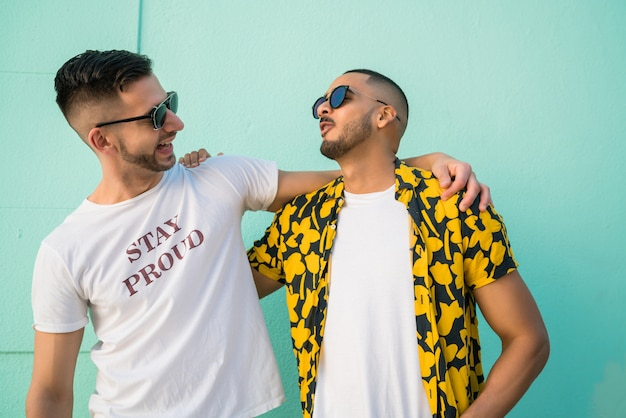 Ritratto di felice coppia gay di trascorrere del tempo insieme e abbracciarsi in strada.