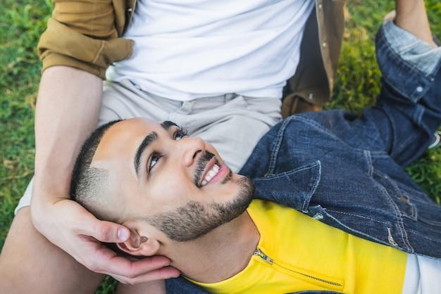 Ritratto di felice coppia gay trascorrere del tempo insieme e avere un appuntamento al parco.