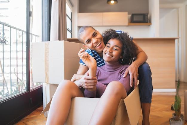 Ritratto di felice coppia latina divertendosi con scatole di cartone nella nuova casa al giorno del trasloco
