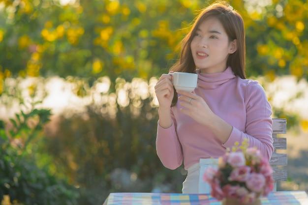 Ritratto di felice donna asiatica che indossa un maglione rosa pensando tenendo una tazza di caffè in un parco in inverno.