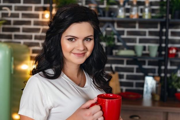 Ritratto di felice donna dai capelli scuri, con in mano una tazza rossa in piedi in cucina