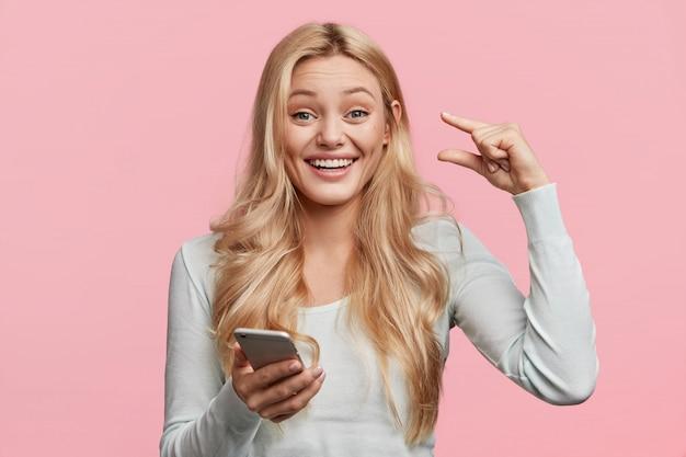 Ritratto di felice felice giovane donna carina mostra la quantità di denaro che ha ricevuto questo mese, tiene in mano il cellulare moderno, legge il messaggio, isolato su un muro rosa. questo è troppo piccolo