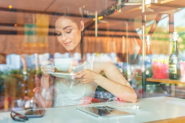 Ritratto di felice giovane donna d'affari con la tazza in mano a bere il caffè al ristorante