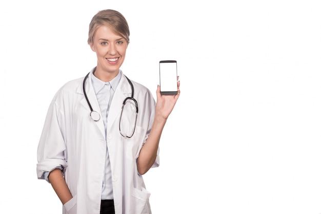Ritratto di felice medico femminile che promuove il telefono astuto. horizonta