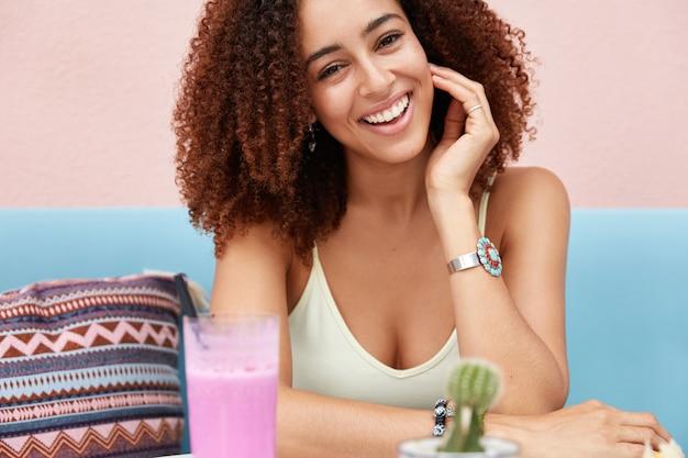 Ritratto di felice modello femminile felicissimo con ampio sorriso splendente, beve cocktail freschi nella caffetteria