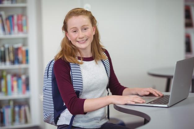 Ritratto di felice studentessa con zainetto utilizzando laptop in libreria