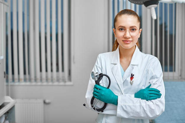 Ritratto di felice successo giovane dottoressa in possesso di uno stetoscopio. concetto medico
