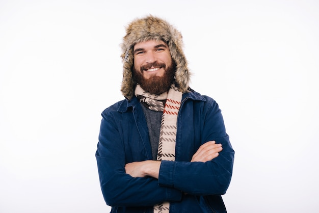 Ritratto di felice uomo barbuto con le braccia incrociate, guardando la fotocamera e indossando abiti invernali