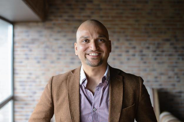 Ritratto di felice uomo d'affari indiano bello, sorridente, fiducioso e amichevole al chiuso.