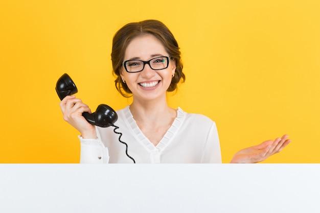 Ritratto di fiduciosa bella eccitata sorridente felice giovane donna d'affari con telefono mostrando cartellone bianco su maglietta gialla
