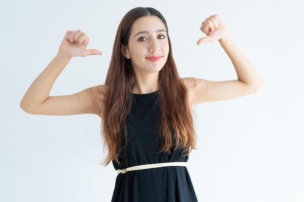 Ritratto di fiduciosa giovane imprenditrice che punta a se stessa