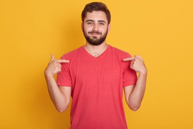 Ritratto di fiducioso bell'uomo caucasico che indossa maglietta casual rossa, in piedi su giallo, che punta sulla sua maglietta
