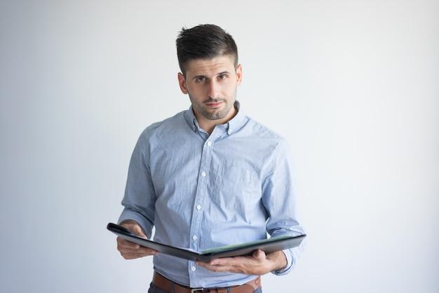 Ritratto di fiducioso giovane imprenditore con cartella aperta.