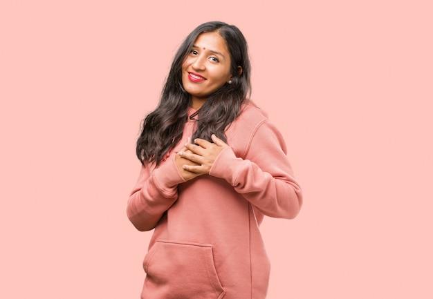 Ritratto di fitness giovane donna indiana facendo un gesto romantico, innamorato di qualcuno o mostrando affetto per qualche amico