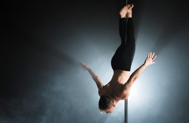 Ritratto di forte modello maschile eseguendo una pole dance