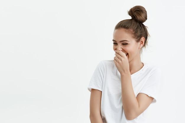 Ritratto di giocosa donna caucasica femminile ridendo mentre guardando lo spazio di copia e coprendo la bocca con la mano