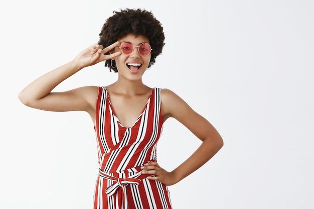 Ritratto di gioiosa donna afroamericana fiduciosa e civettuola in tuta a righe, tenendo la mano sul fianco, mostrando il gesto di vittoria sopra gli occhi e sorridente