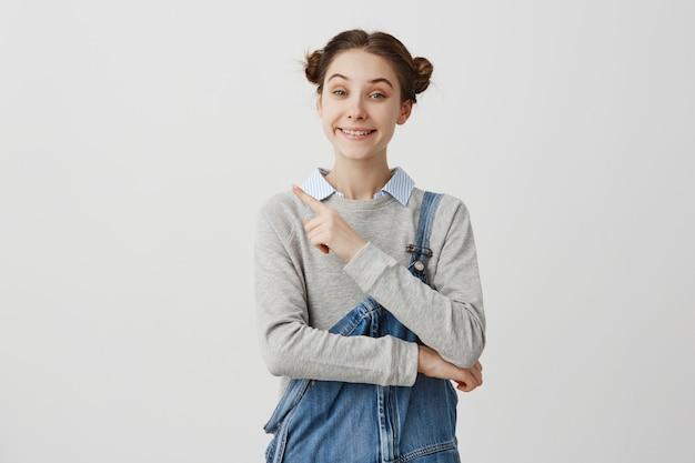 Ritratto di gioiosa giovane donna che indossa jeans che punta il dito di distanza. emozioni positive della ragazza che gesturing sulla parete bianca che propone i servizi. copia spazio