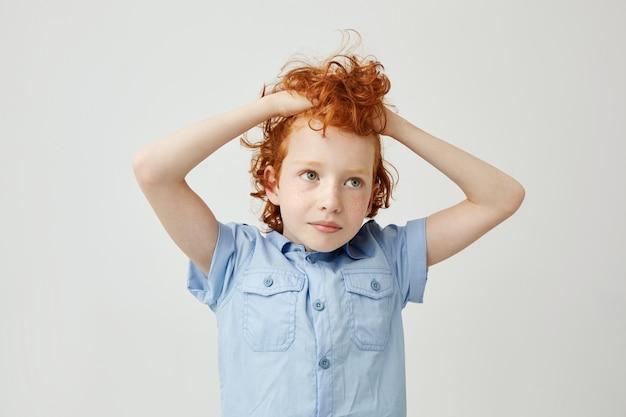 Ritratto di gioioso piccolo ragazzo allo zenzero con capelli ondulati e lentiggini tenendo i capelli con le mani, guardando da parte con espressione stanca e annoiata.