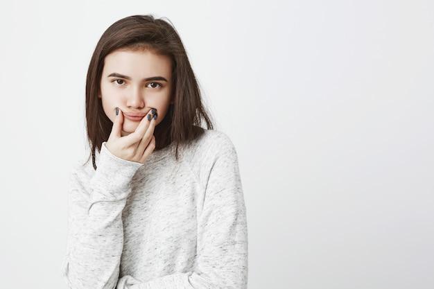 Ritratto di giovane adolescente tenebroso che esprime insoddisfazione tenendo la bocca con le mani per imitare il sorriso