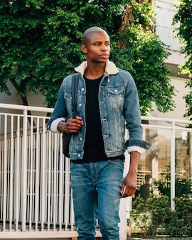 Ritratto di giovane africano rasato con zaino all'aperto