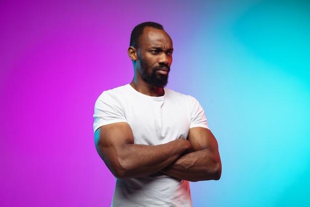 Ritratto di giovane afro-americano su studio gradiente in neon