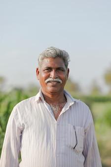 Ritratto di giovane agricoltore indiano, campo agricolo