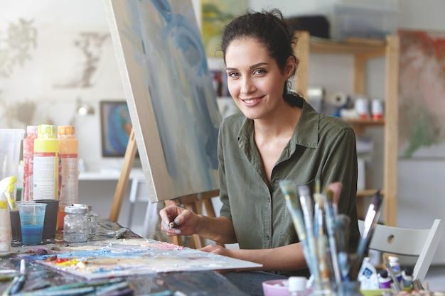 Ritratto di giovane artista femminile di talento che fa schizzi con oli luminosi, disegno su cavalletto, con un sorriso piacevole. pittore sorridente che è occupato con il suo lavoro all'officina. arte, concetto di creatività