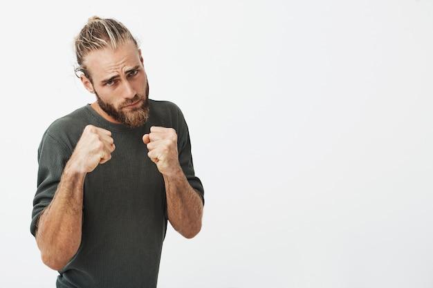 Ritratto di giovane attraente con acconciatura alla moda e barba tenendosi per mano davanti a lui in posizione di boxe andando a combattere.