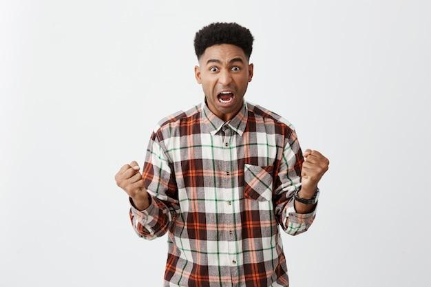 Ritratto di giovane attraente dalla pelle scura con acconciatura afro in camicia a scacchi casual gesticolando con le mani, urlando a gran voce, incoraggiando la sua squadra di calcio preferita sullo stadio.