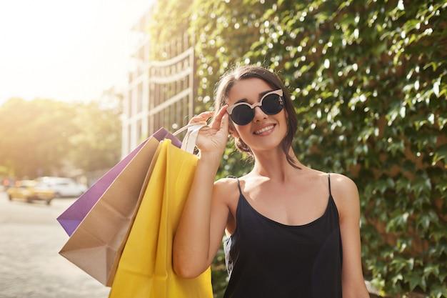 Ritratto di giovane attraente donna europea dai capelli castani in occhiali da sole e abiti neri, sorridente a porte chiuse, tenendo una grande quantità di borse per la spesa dopo aver acquistato regali per gli amici.