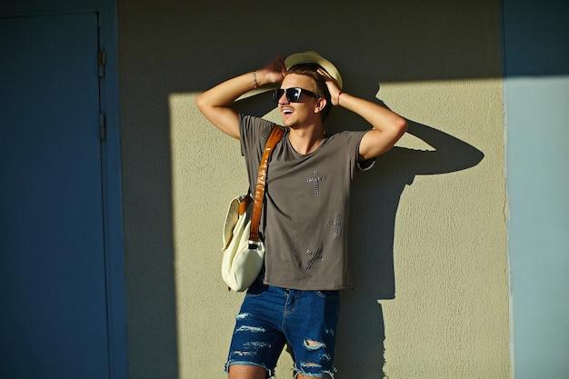 Ritratto di giovane attraente elegante uomo moderno sorridente in panno casual nel cappello in occhiali da sole in piedi vicino al muro